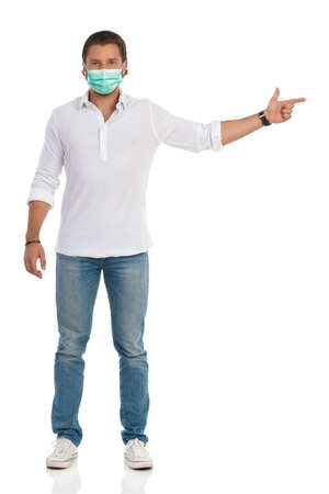 Handsome young man in protective face mask is standing and pointing at the side. Front view. Full length studio shot isolated on white.