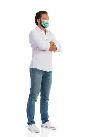 Casual man in protective face mask is standing with arms crossed and looking away. Full length studio shot isolated on white.