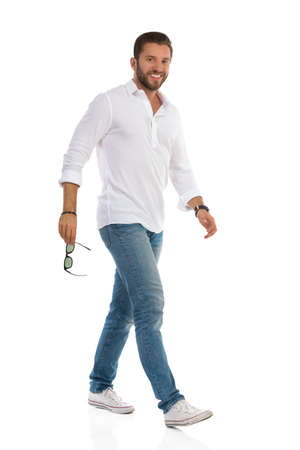 Casual young handsome man is walking, holding sunglasses, looking at camera and smiling. Side view. Full length studio shot isolated on white.