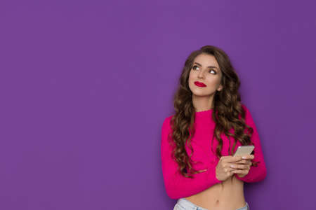 Young woman in neon pink sweater is holding telephone, looking away and thinking. THree quarter length studio shot on purple background.