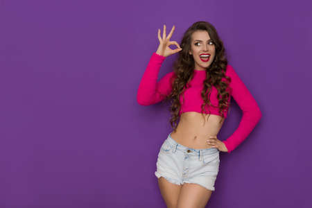 Happy young woman in a short neon pink sweater and jeans shorts is showing ok hand sign and talking. Three quater length studio shot on purple background.