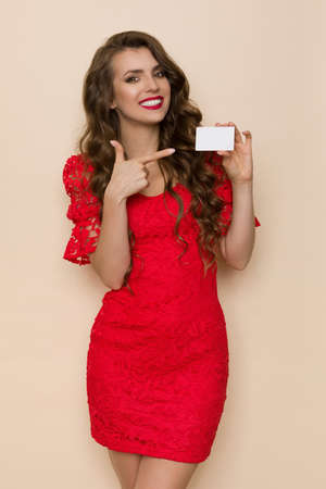 Smiling young woman in elegant red lace dress is holding white gift card and pointing at it. Three quarter length studio shot on beige background.