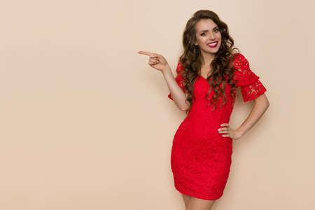 Beautiful young woman in elegant red lace dress is pointing at the side and smiling. Three quarter length studio shot on beige background. Standard-Bild