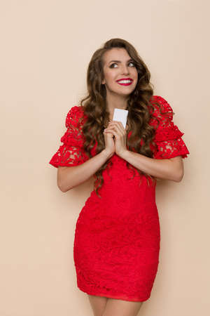 Excited young woman in elegant red lace dress is holding white gift card, looking away and smiling. Three quarter length studio shot on beige background.