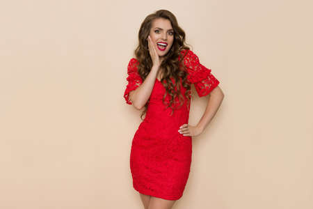 Surprised young woman in elegant fitted red lace mini dress is holding hand on chin and shouting. Three quarter length studio shot on beige background.