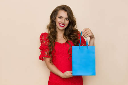Beautiful young woman in elegant red lace dress is showing blue shopping paper bag and smiling. Waist up studio shot on beige background.