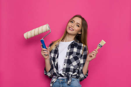 Smiling young woman in lumberjack shirt is holding paintbrush and paint roller. Front view. Waist up studio shot on pink background. Standard-Bild