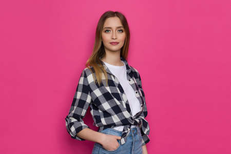 Portrait of young woman in lumberjack shirt. Waist up studio shot on pink background.