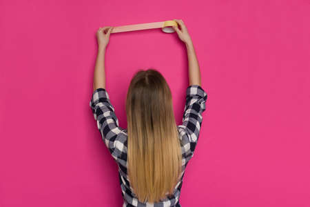 Young blond woman in lumberjack shirt is holding yellow painter's tape on pink wall. Rear view. Waist up shot. Standard-Bild