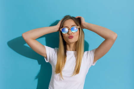 Young blond woman in white shirt and sunglasses is posing with head in hands and sending a kiss. Waist up shot on blue background.