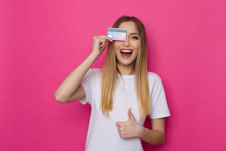 Laughing young woman in white shirt covers eye with credit card and gives thumb up. Waist up studio shot on pink background. Standard-Bild