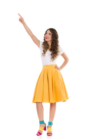 Happy young woman in white yop, yellow skirt and colorful high heels is looking up, holding arm raised and pointing over the head. Front view. Full length studio shot isolated on white.
