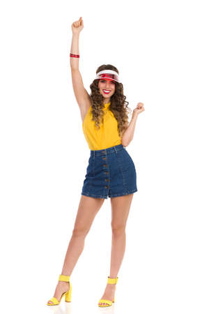 Happy young woman in high heels sandals, jeans mini skirt, yellow top and red sun visor is standing with arm raised and smiling. Front view. Full length studio shot isolated on white. Standard-Bild