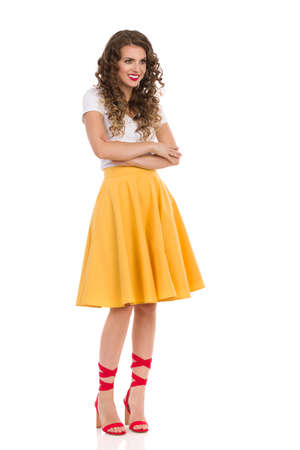 Beautiful young woman in yellow skirt, white top and red high heels is standing with arms crossed, looking away and smiling. Full length studio shot isolated on white.