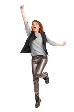 Young woman in gray blouse, shiny pants and black boots is jumping with arm raised and shouting. Full length studio shot isolated on white. Foto de archivo