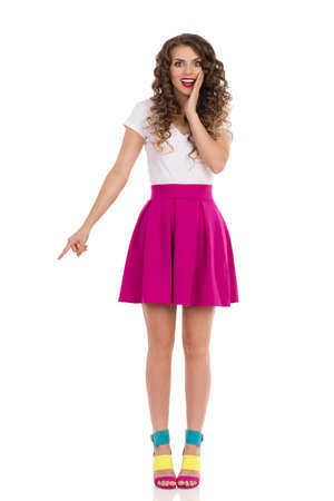 Excited young woman in colorful high heels, pink mini skirt and white top is standing, holding hand on chin and pointing down. Front view. Full length studio shot isolated on white. Stockfoto