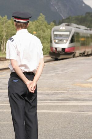 conductor: Conductor standing on platform waiting for the train to arrive
