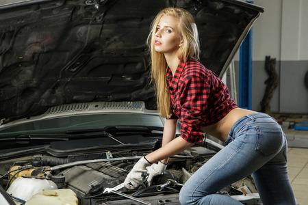 Mooi meisje monteur reparatie van een auto