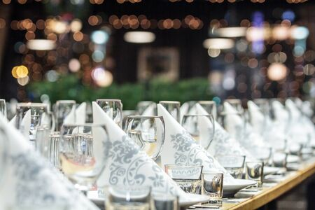serviettes: A long banquet table with wineglasses and serviettes, view from the left side Stock Photo