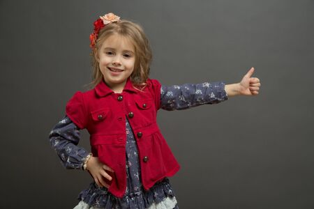 gives: Sweet little girl in a red and blue dress gives thumbs up