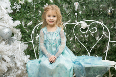 2 persons: Happy little girl in a suit of the Snow Queen is sitting alone and smile near the Christmas tree on a bench for 2 persons