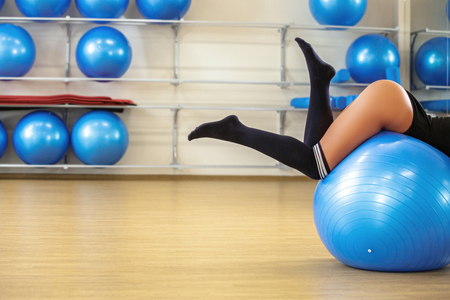 blue ball: Young woman doing exercise on blue fitness ball in the gym