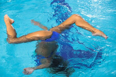nataci�n sincronizada: Beautiful girl is engaged synchronized swimming in pool