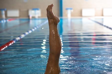 Het mooie meisje is bezig gesynchroniseerde zwemmen in het zwembad Stockfoto