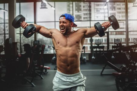 free weights: Handsome man lifting dumbbells at gym. Free weights. Stock Photo
