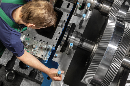 steam turbine: Working man with a small steam turbine. Metal gears. Gear wheels of the engine. Stock Photo