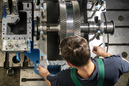 turbina de vapor: Hombre de funcionamiento limpie las partes una peque�a turbina de vapor. Engranajes del metal. Ruedas de engranaje del motor.