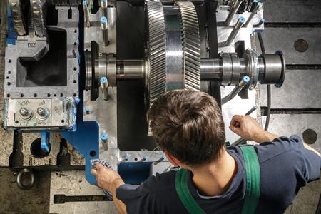 steam turbine: Working man clean parts a small steam turbine. Metal gears. Gear wheels of the engine.