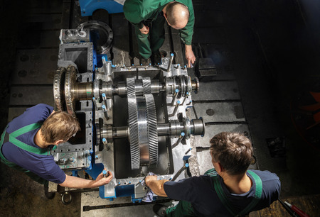 turbina de vapor: las personas que trabajan con una peque�a turbina de vapor. Engranajes del metal. Ruedas de engranaje del motor. Foto de archivo