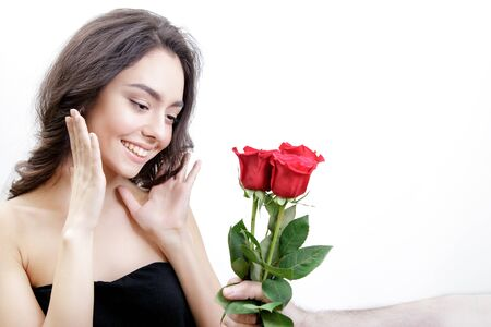 receiving: Beautiful girl receives three red roses. She is surprised, looking at the flowers and smiling. Mens hand holding three roses. Girl is white with bushy brown hair. Isolated on white background. Stock Photo