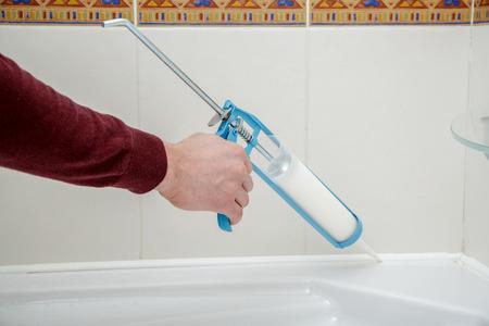 caulk: Plumber hand applying silicone sealant with caulking gun in the bathroom.