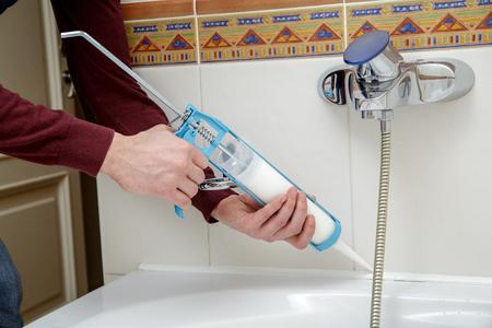Man hands applying silicone sealant with caulking gun.