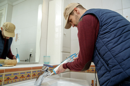 silicone: Man applying silicone sealant with caulking gun in the bathroom.
