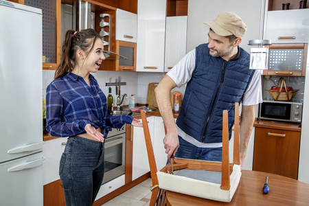 shrugs: Handyman repairing furniture in the kitchen. He repairs a chair with a screwdriver. The man looks at a housewife and smiling. The woman looks at him, smiles and shrugs. She wonders.