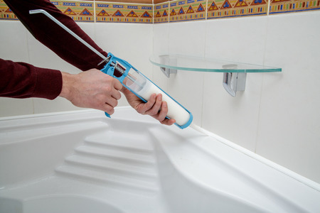 Man hands applying silicone sealant with caulking gun.