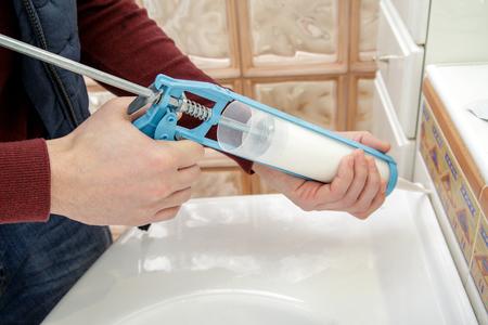 caulk: Worker hands applying silicone sealant with caulking gun.