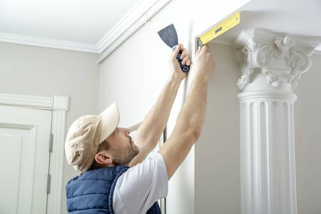 finishing: Worker holds putty knife and measures the wall corner using metal angle. Finishing work.
