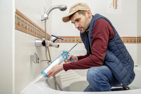 caulk: Plumber caulking bathtub with silicone glue using caulking gun.