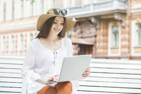 Happy young woman working with a laptop sitting on a bench. She smiles. Student is white with brown hair. The woman dressed in brown jeans, a white tunic. On her head is hat and sunglasses. Summer day. Stock Photo