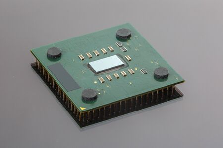 microelements: CPU. Modern computer processor unit. The microprocessor is located on a green PCB. 4 mounting pads on the card and microelements around the processor chip. Isolated on gray. Pins reflection.