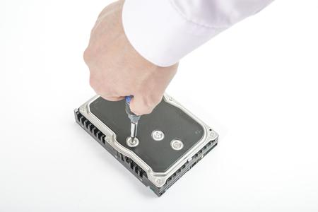 disco duro: El reparador manual desenrosca la tapa del disco duro de 3,5 pulgadas con un destornillador. Aislado en el fondo blanco.