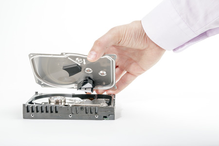 hard disk: Hand repairman opens the top cover of the 3.5 inch HDD. Isolated on white background. Stock Photo