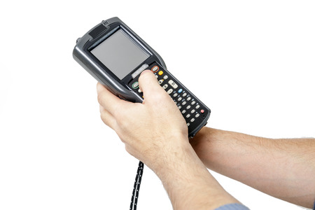 Mans hand holding a barcode scanner. His second hand presses the button on the scanner keyboard. The scanning device is directed upwards to the left. Isolated on white background.
