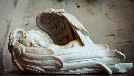 angel figurinу of an angel against the background of a white wall Christmas decor, white countertop, white wall, bokeh, background,