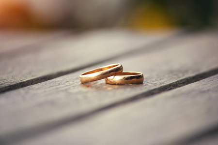 Golden rings of newlyweds against the background of a wooden table