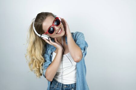 blond woman in headphones and sunglasses listening to music white background Stock fotó